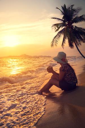 vacaciones en la playa: Silueta vista lateral de feliz joven hermoso sombrero de paja del desgaste de mujer - sentarse en la playa en verano a la hora de la puesta del sol. tono de color de la vendimia