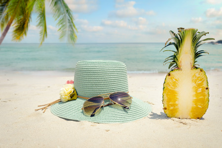 Summer vacation concept straw hat with sunglasses and pineapple fruit on sandy tropical beach