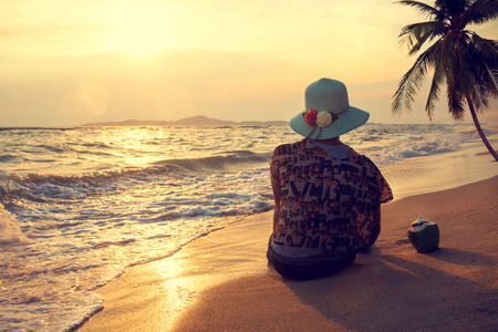 view woman: Silhouette rear view of happy beautiful young woman wear straw hat - sit on the beach in summer at sunset time. Vintage color tone