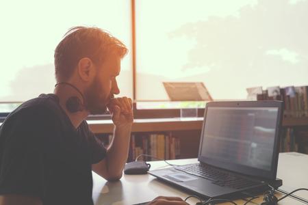 若いビジネス人手彼のラップトップに取り組んで忙しいの横顔発砲。男子生徒は、ライブラリ内のテーブルに座ってノート パソコンを使ったします