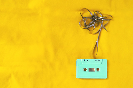 Top view of cassette tape over yellow background with tangled ribbon. retro filter effect and vintage style Фото со стока