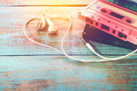 나무 테이블에 이어폰 심장 모양의 복고풍 테이프 카세트의 상위 뷰 (위) 샷. 음악 개념을 사랑 - 빈티지 색상 효과 스타일을