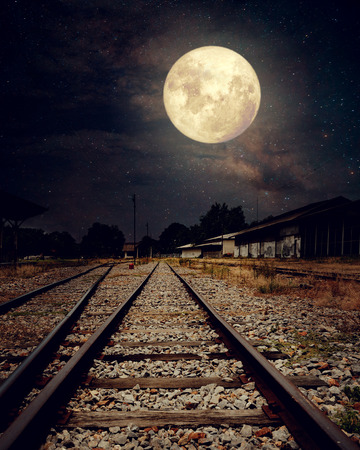 voyage: Beautiful countryside Railroad with Milky Way star in night skies, full moon - Retro style artwork with vintage color tone (Elements of this moon image furnished by NASA)