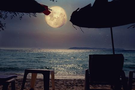 Piękna tropikalna plaża fantasy z gwiazdą Drogi Mlecznej na nocnym niebie, pełnia - grafika w stylu retro z klasycznym odcieniem kolorów (elementy tego księżycowego obrazu dostarczone przez NASA)