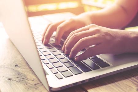 Vue de côté plan des mains belle jeune femme hipster occupé à travailler sur son ordinateur portable assis à table en bois dans un café - effet de filtre rétro et style de couleur cru