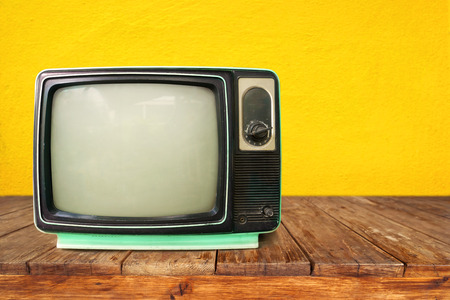 レトロなテレビ - ヴィンテージの技術の木のテーブルで古いテレビ
