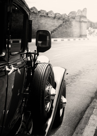 black car: Old classic car parked on street in urban - vintage black and white vintage film grain filter effect styles