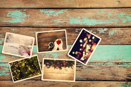 古い木製のテーブルの上のメリー クリスマス (クリスマス) フォト アルバム。ポラロイド カメラ - ヴィンテージやレトロなスタイルの紙の写真