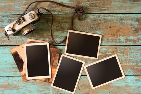 レトロなカメラと木製のテーブル - 空白のフォト フレーム ビンテージ スタイルの空古いインスタント紙フォト アルバム
