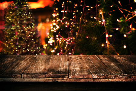 christmas display: Christmas and New year background with empty dark wooden deck table over christmas tree and blurred light bokeh. Empty display for product montage. Rustic vintage Xmas background.