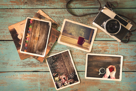 vintage photo: Merry christmas (xmas) photo album on old wood table. paper photo of polaroid camera - vintage and retro style
