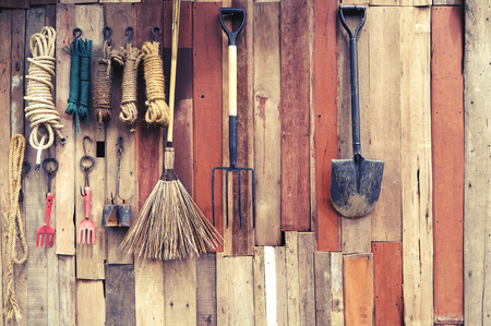 agricultural tools hang on wooden wall in farm - rural vintage style Stock Photo