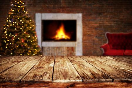 Kerstmis en Nieuwjaar achtergrond met lege donkere houten dek tafel over kerstboom en wazig licht bokeh. Lege display voor product montage. Rustieke vintage Kerstmis achtergrond.