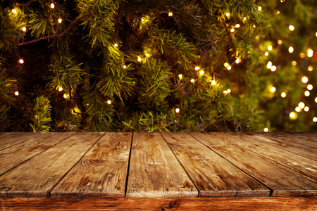 empty table: Christmas and New year background with empty dark wooden deck table over christmas tree and blurred light bokeh. Empty display for product montage. Rustic vintage Xmas background.