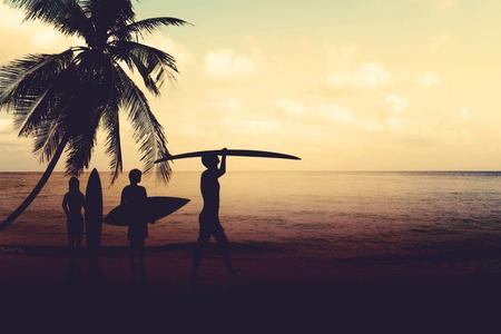 日没 - ヴィンテージ色のトーンでビーチでサーファーをシルエットのアート フォト スタイル 写真素材