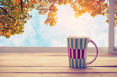 Hot coffee cup on wood table in fall season. autumn tree background with blue sky. vintage color tone