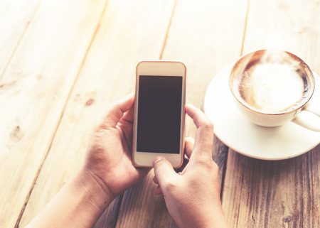 Close up of beautiful young hipster womans hands holding mobile smart phone with hot coffee cup at cafe shop, female using cell telephone with blank copy space screen for your advertising text message. vintage color tone Stock Photo