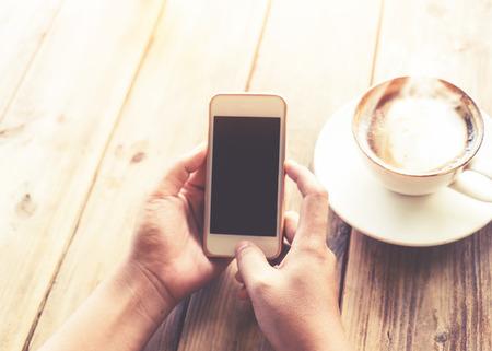 Close-up van de handen van mooie jonge hipster vrouw met mobiele smart phone met warme kopje koffie bij cafe winkel, vrouw met behulp van mobiele telefoon met blanco exemplaar ruimte scherm voor uw reclame tekstbericht. vintage kleurtoon Stockfoto