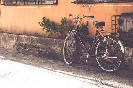 bicicleta de la vendimia estacionado en la pared de edad en la estrecha calle urbana (cosecha de color estilos de tono) Foto de archivo