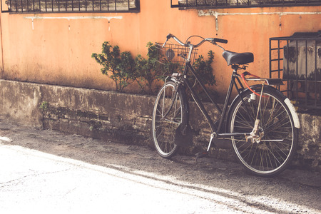 vintage bicycle parked at old wall in the urban narrow street (vintage color tone styles) Stock Photo