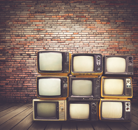 Antique and vintage style photo. retro televisions pile on floor in old room.