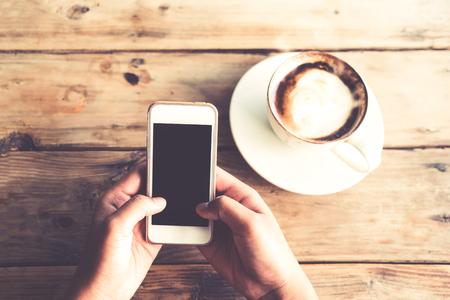 Cerca de las manos de la mujer hermosa joven inconformista que sostienen el teléfono móvil inteligente con la taza de café caliente en la tienda de café, mujer que usa el teléfono celular con pantalla de copia espacio en blanco para su mensaje de texto publicitarios. tono de color de la vendimia Foto de archivo