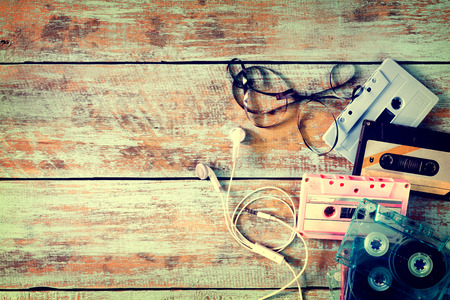 Top view (above) shot of retro tape cassette with earphone on wood table - vintage color effect styles. Stock Photo