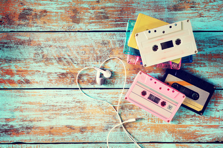 earphone: Top view (above) shot of retro tape cassette with earphone heart shape on wood table. Love music concept - vintage color effect styles