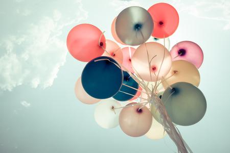 Globos de colores volando en el cielo con un efecto retro filtro de la vendimia. El concepto de feliz cumpleaños en verano y fiesta de boda luna de miel - uso para el fondo (tono de color de la vendimia)