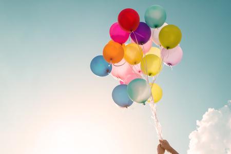 Hände des Mädchens halten mehrfarbige Ballons mit einem Retro-Vintage-Filter-Effekt, Konzept der Happy Birthday im Sommer und Hochzeit Flitterwochen Party (Vintage Farbton)