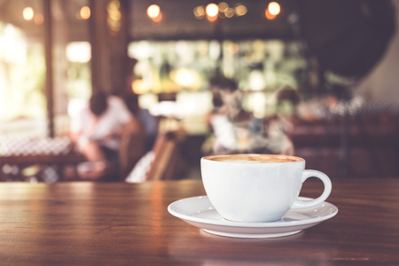 Cup of hot coffee on table in cafe with people. vintage and retro color effect - shallow depth of field