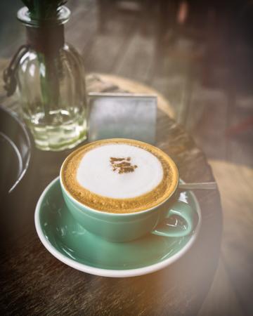 capuchino: capuchino caliente en la taza de café verde en la mesa de madera en el café. doble exposición y ligeras fugas de época filtran estilo del efecto. Foto de archivo