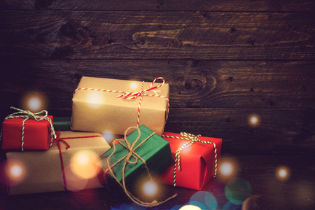 christmas present box: Christmas present gifts box and light bokeh on old wooden background. vintage color tone Stock Photo