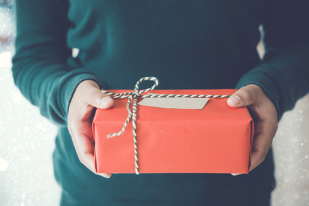 christmas present box: Woman hands holding Christmas handmade gift box or new year present with snow background. vintage color tone