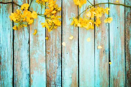Yellow flowers on vintage wooden background, border design. vintage color tone - concept flower of spring or summer background 스톡 콘텐츠