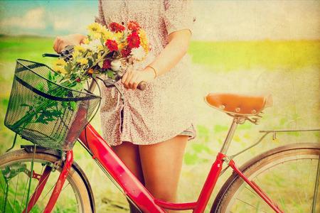 빨간 자전거의 바구니에 다채로운 꽃으로 봄에서 여자 라이프 스타일. 사진 빈티지 색상 톤 스타일.