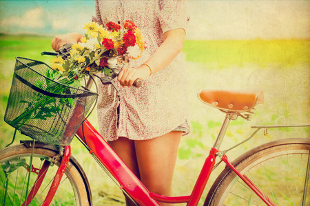 Woman lifestyle in spring with colorful flowers in basket of red bicycle. photo vintage color tone styles.