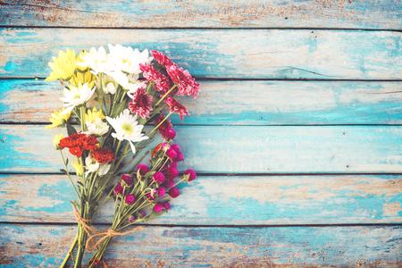 Colorful flowers bouquet on vintage wooden background, border design. vintage color tone - concept flower of spring or summer background
