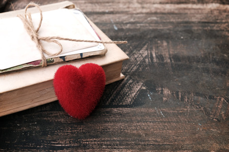 novel: Red heart and vintage novel book - concept of love story nostalgia and remembrance in valentines day. vintage color tone