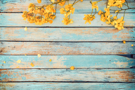 Yellow flowers on vintage wooden background, border design. vintage color tone - concept flower of spring or summer background 写真素材