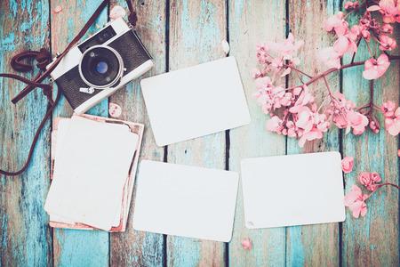 Retro camera en lege oude onmiddellijke papier fotoalbum op houten tafel met bloemen grens ontwerp - concept van herinnering en nostalgie in het voorjaar. vintage-stijl Stockfoto