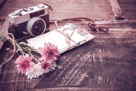 Uitstekende camera met boeket van bloemen op oude houten achtergrond - concept van nostalgisch en herinnering op de lente uitstekende achtergrond