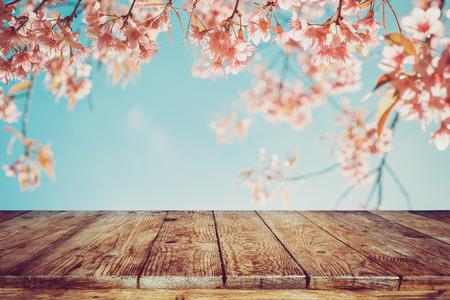 봄 시즌 - 빈 귀하의 제품 및 음식 표시 또는 몽타주에 대 한 준비 하늘 배경에 분홍색 벚꽃 꽃 (사쿠라) 나무 테이블의 상단. 빈티지 색조입니다.