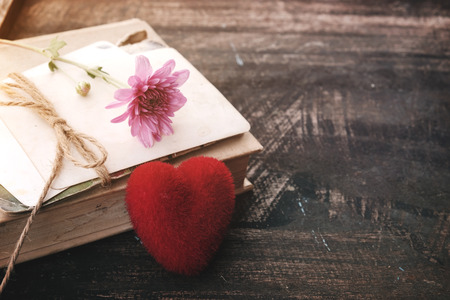Red heart and vintage novel book - concept of love story nostalgia and remembrance in valentines day. vintage color tone