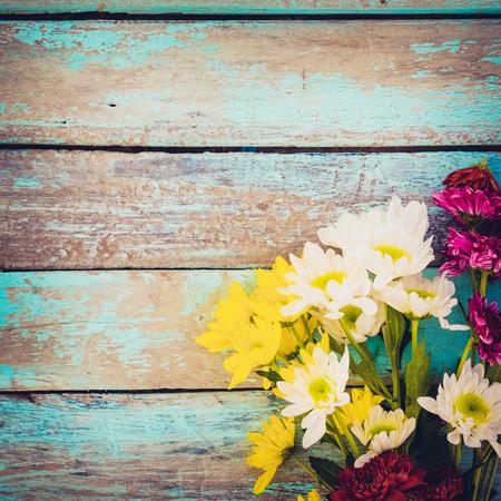 Kleurrijk bloemenboeket op uitstekende houten achtergrond, grensontwerp. vintage kleurtoon - concept bloem van lente of zomer achtergrond