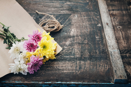 paper craft: Beautiful flower bouquet wrapped in craft paper on the wooden table background. vintage color tone.