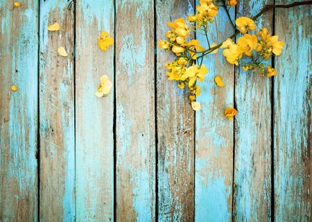 빈티지 나무 배경에 노란색 꽃, 테두리 디자인. 빈티지 색조 - 봄 또는 여름 배경의 개념 꽃
