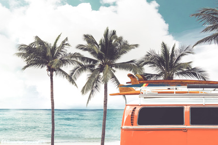 Vintage car parked on the tropical beach (seaside) with a surfboard on the roof - Leisure trip in the summer. retro color effect
