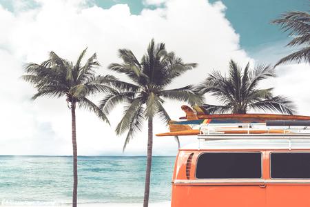 Weinleseauto parkte auf dem tropischen Strand (Küste) mit einem Surfbrett auf dem Dach - Freizeitreise im Sommer. Retro-Farbeffekt