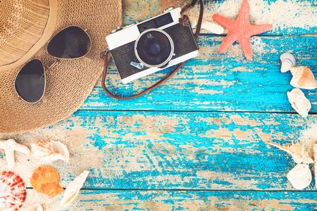 Sommer-Hintergrund - Das Konzept der Urlaubsreisen im Sommer auf einem tropischen Strand am Meer. Retro-Kamera mit Seesternen, Muscheln, Korallen auf Holztisch Hintergrund. Vintage-Farbton Stile. Standard-Bild